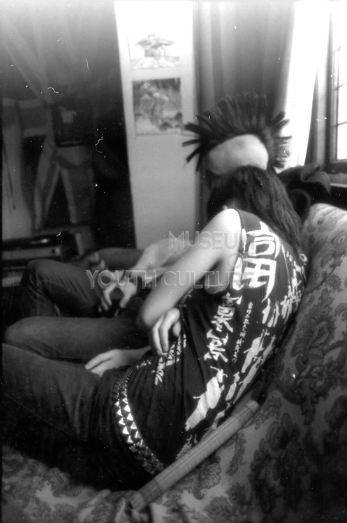 Two punks on a settee, UK. 1980s.