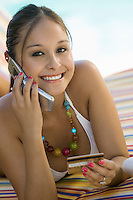 Girl Holding Credit Card and Using Cell Phone