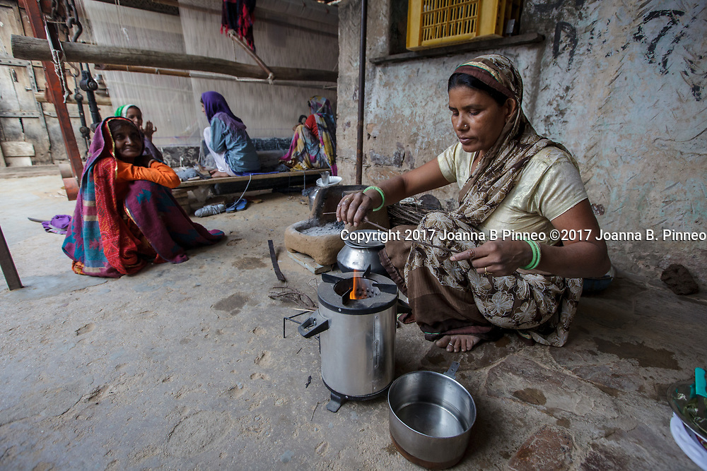 "Shanti Bai makes tea for visitors and her employees using her Greenway Smart Stove to make the tea.  Greenway stoves are made in India. Greenway says that their stoves deliver 60% fuel savings and 70% smoke reduction than the traditional ""chulha"" or mud stove. Shanti Bai runs a weaving business out of her home with seven looms and twenty-eight women employees. She is part of the Jaipur Rug Foundation weavers. Shanti also uses LPG to cook larger meals and the ""chuhla"" to cook the chapati or flatbread that is a staple in Indian homes. Often families who have switched to cleaner cooking stoves still practice ""stove stacking"" which is using more than one type stove at a time, usually the traditional stove and the cleaner one. Some use the traditional stove for specific types of traditional food and some use both at the same time. It can take time for the family cook, usually the woman, to switch completely to the cleaner cooking stove."