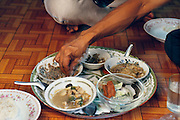 Khuenkaew family meal of rice, cucumbers, red pork, bamboo shoot stew, and shrimp-paste. The family sits on the floor to eat dinner. The Khuenkaew family lives in a wooden 728-square-foot house on stilts, surrounded by rice fields in the Ban Muang Wa village, outside the northern town of Chiang Mai, in Thailand. Published in Material World, page 177.