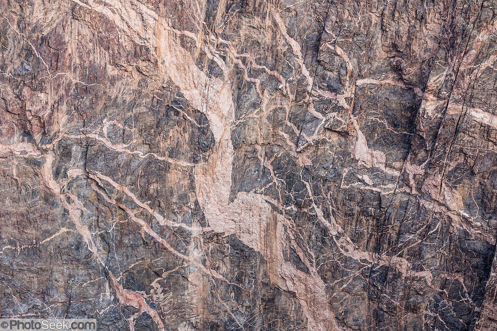 From Dragon Point, see fanciful patterns of pegmatite intrusions on the Painted Wall, in Black Canyon of the Gunnison National Park, near Montrose, Colorado, USA. Pressurized molten rock was forced into 1.7-billion-year-old metamorphic rock, forming pink pegmatite stripes on Colorado's highest cliffs. With two million years to work, the Gunnison River and weathering have sculpted a vertical wilderness of rock, water, and sky.