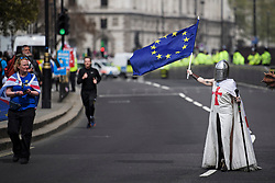 © Licensed to London News Pictures. 23/04/2019. London, UK. A Pro EU campaigner, dressed as St. George, the patrol saint of England, walks next to The Houses of Parliament in London on St. George's Day.. Number 10 will continue talks with labour today in an attempt to reach a compromise on the withdrawal agreement from the EU. Photo credit: Ben Cawthra/LNP