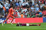 Aston Villa striker Jonathan Kodjia (22) lies dejected as as Fulham goalkeeper David Button (27)  celebrates during the EFL Sky Bet Championship play-off final match between Fulham and Aston Villa at Wembley Stadium, London, England on 26 May 2018. Picture by Dennis Goodwin.