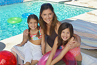 Mother embracing two daughters by swimming pool, portrait