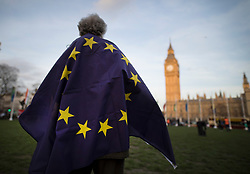 © Licensed to London News Pictures. 13/03/2017. London, UK. A man stands wrapped in a European Union flag in Parliament Square as protestors gather to defend EU migrants' right to remain in the UK after Brexit.  Parliament is expected to pass the Brexit bill this week allowing the Prime Minister to trigger Article 50. Photo credit: Peter Macdiarmid/LNP