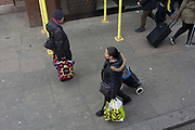 Two women shoppers each carry supermarket plastic bags with fruit designs, on 23rd March 2019, in London, England.