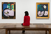"""UNITED KINGDOM, London: 06 March 2018 A visitor takes a look at Picasso's """"Nude in a Black Armchair"""" 1932 (left) and """"Nude, Green Leaves and Bust"""" 1932 (right) at The Tate Modern's new exhibition 'Picasso 1932: Love, Fame, Tragedy'. The exhibition, which consists of a wide range of Picasso works, runs from 8th March - 9 September 2018.  Rick Findler / Story Picture Agency"""