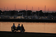 family sitting on a bench overlooking the marina at sunset
