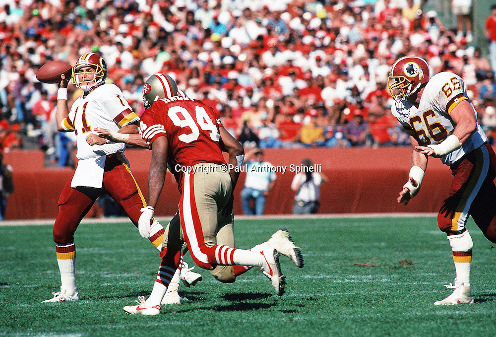Washington Redskins quarterback Mark Rypien (11) throws a pass while being rushed by San Francisco 49ers linebacker Charles Haley (94) while Redskins offensive tackle Joe Jacoby (66) runs toward the action during the NFL football game against the San Francisco 49ers on Sept, 16, 1990 in San Francisco. The 49ers won the game 26-13. (©Paul Anthony Spinelli)