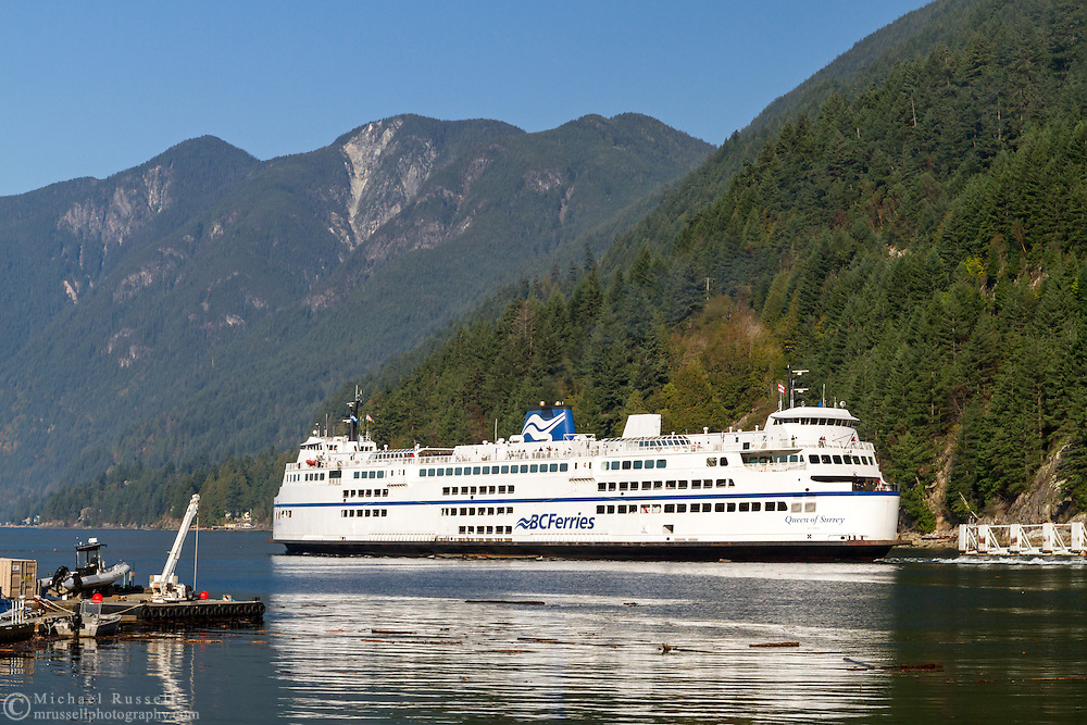 The BC Ferries' Queen of Surrey departs the Horseshoe Bay Ferry Terminal on a return trip from the Sunshine Coast.  Photographed from Horseshoe Bay Park in Horseshoe Bay, British Columbia, Canada. Howe Sound and Saint Mark's Summit, Unnecessary Mountain, Mount Harvey, Brunswick Mountain (of the  Pacific Ranges and Coast Mountains) are in the background.