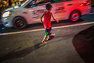 Young boy navigates through traffic with a single skate (he only has one) in the Malate restaurant and red-light entertainment district at around midnight.  Malate, Manila, Philippines.
