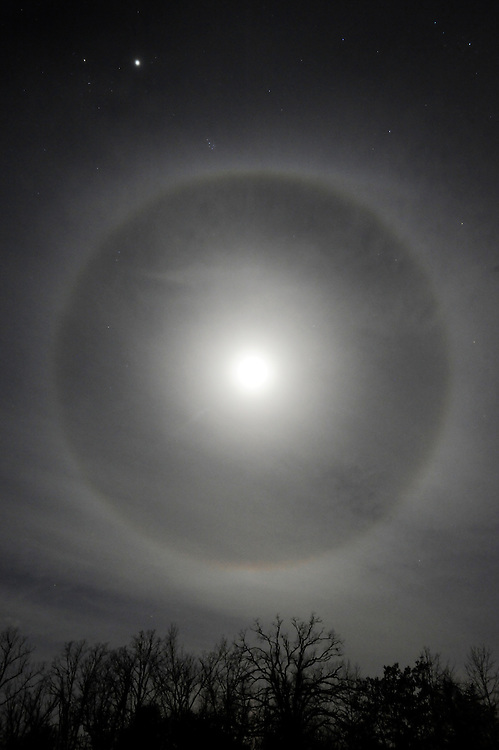 A halo of light rings a full moon on a winter night in Baxter County, Arkansas.