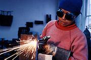 A woman welder operating a blow torch
