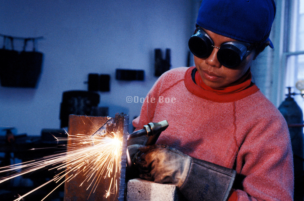 A woman welder operating a blow torch