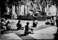 Women praying at Shwedagon Pagoda, Yangon, Burma.