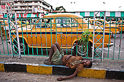 A homeless man lies asleep on the pavement outside the busy Kolkata train station.  Yellow taxis wait to collect passengers.