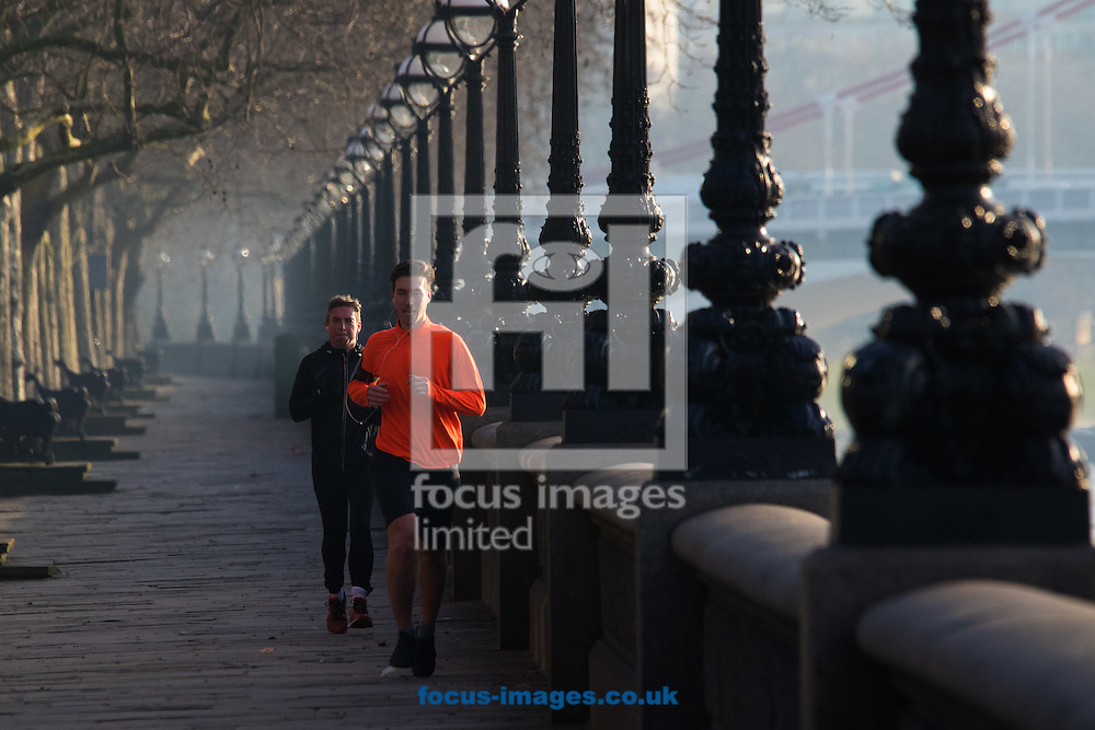 Two runners enjoy the morning sunshine as they jog along the River Thames on Cheyne Walk, London <br /> Picture by Paul Davey/Focus Images Ltd +447966 016296<br /> 24/02/2016