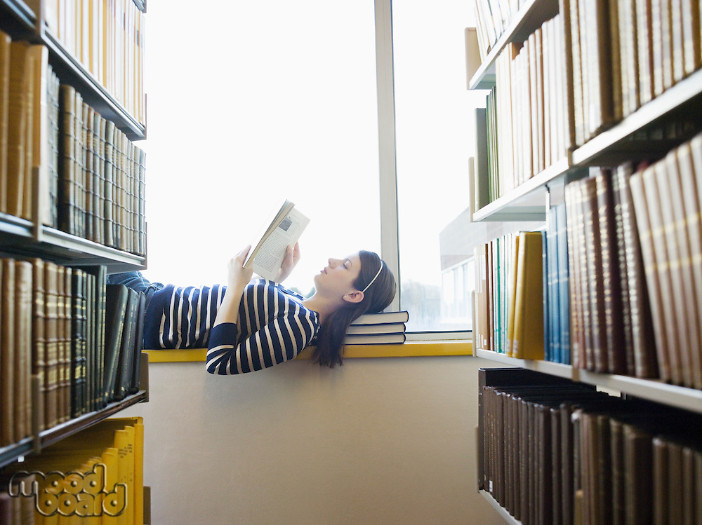 Student lying down on windowsill in library reading