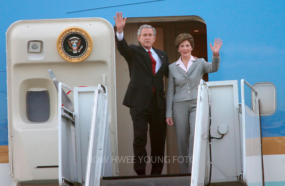 epa00863383 US President George W. Bush (L) and first lady Laura Bush wave as they disembark from the plane upon their arrival in Singapore on Thursday 16 November 2006. Bush opens his one week long Asia tour with a visit to Singapore.  EPA/HOW HWEE YOUNG