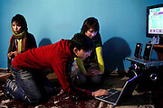 Elaha Soroor, 20, (right) a finalist for 'Afghan Star', a Tolo TV program similar to American Idol, is listening to some of her songs with her younger brother (centre) and a female member of her music group (left) in her home in Kabul, Afghanistan. Elaha Soroor was a finalist of Afghan Star in the 2008-2009 edition but failed to win on the final night. Some believe she lost because of her gender, others believe because she is ethnically Hazara, a minority group constituting about 15% of Afghanistan's population with features similar to Mongolians, flat noses, broad faces and almond-shaped eyes. Hazaras are mostly Shia Muslims, as opposed to other Afghans who are for the most part Sunnis.