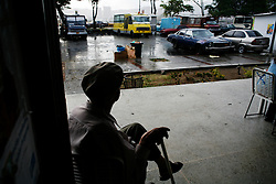 An old man sits waiting for the rain to stop outside a bakery which was setup by Alexis Vive to raise funds for the collective.
