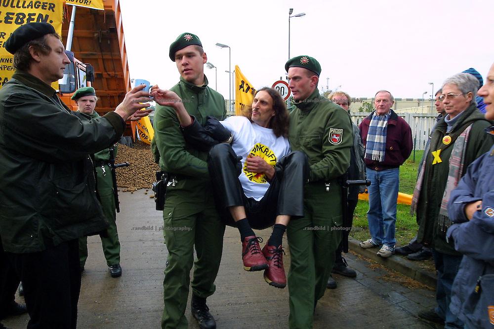 Francis Althoff, Mitglied des Vortsand der Bürgerinitiative Umweltschutz, wird von der Polizei weggetragen. Er war an einer Blockade des Zwischenlagers Gorleben beteiligt. Während der Polizeiaktion reicht Althoff seine Kaffeetasse an einen Demonstranten weiter.