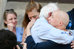 Sen. Bernie Sanders (I-VT) hugs patient Maria Garcia of stage as the presidential candidate is joined by hospital workers, union members and local politicians to protests the imminent closure of Hahnemann University Hospital at a rally in Philadelphia, PA on July 15, 2019. The struggling Center City located hospital announced it will seize operations and is facing out critical services like Emergency access and the maternity ward unless support is found to end the financial turmoil