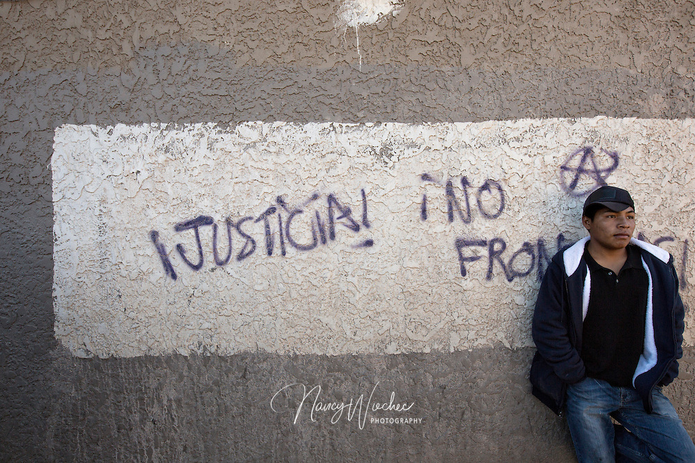 "A man leans against a wall near the international border in Nogales, Sonora, Dec. 20. The graffiti reads, ""Justice! No Borders!"" (CNS photo/Nancy Wiechec)"