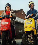 Two teenagers sitting on their mopeds one red one yellow outside a garage.
