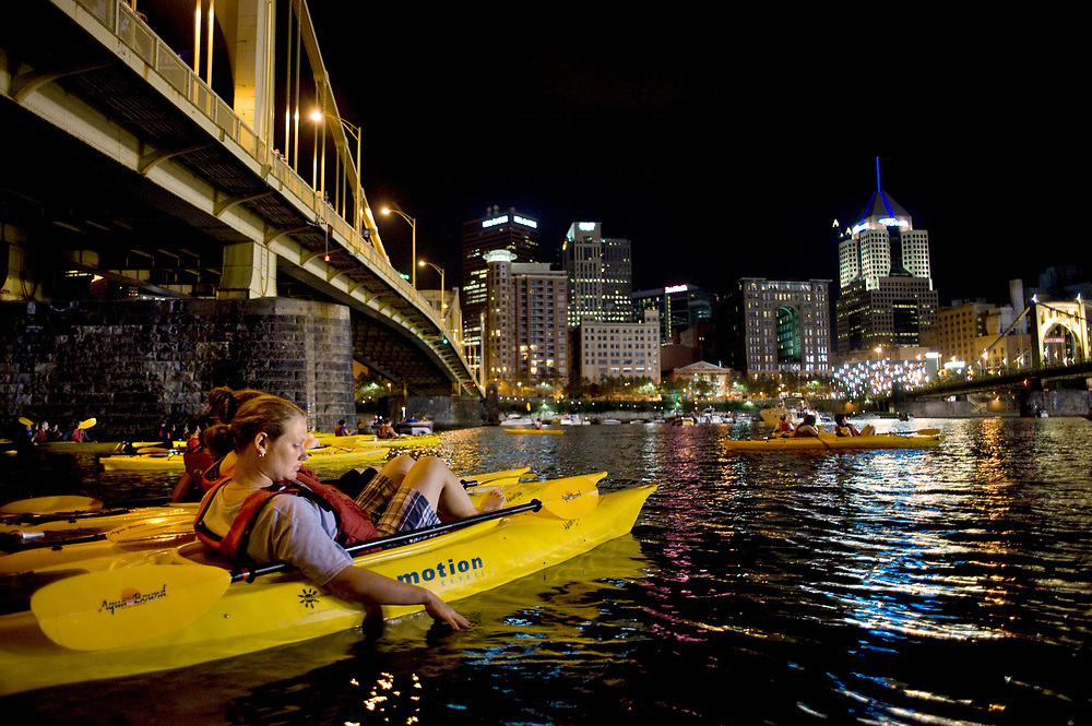 Michelle Hellinger, of Louisville, Kentucky, dips her fingers into the Allegheny River in Pittsburgh while participating in Venture Outdoors' Fireworks Paddle.