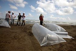 21 May 2010. Grand Isle, Lafourche Parish, Louisiana. .BP Macondo Well disaster. Clean up crews contracted by BP commence the process of clearing oil, (and journalists where they can) from the beaches. Oil washes ashore in greater concentrations than previously seen on the once pristine beaches of Grand Isle. The economic and environmental impact is devastating with shrimp boats tied up, vacation rentals and charter boat fishing trips cancelled as police chase tourists from the beaches just two hours drive from New Orleans..Oil from the Deepwater Horizon catastrophe is evading booms laid out to stop it thanks in part to the dispersants which means the oil travels at every depth of the Gulf and washes ashore wherever the current carries it. .Photo credit; Charlie Varley.
