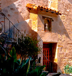 SUBJECT: Carmel Mission Belltower IMAGE: Shadows combine with stairs, door and roof overhang to create a pattern against the stone walls of the belltower at the Carmel Mission, California