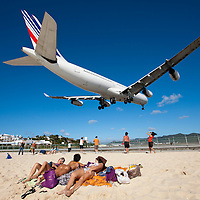 Dutch Antilles, Sint Maarten, Landing Air France jet flies over scantily clad sunbathers on beach at end of landing strip of Princess Juliana International Airport