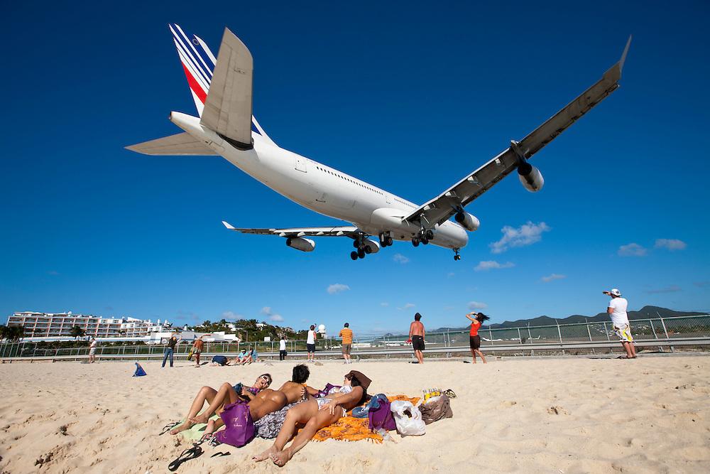 Dutch Antilles, Sint Maarten, Landing Air France jet flies over scantily clad sunbathers on beach at end of landing strip of Princess Juliana International Airport