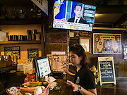 09 NOVEMBER 2016 - BANGKOK, THAILAND:   A Thai waitress at Roadhouse Barbecue rings up an order while CNN election coverage is on the TV above her. Democrats Abroad Thailand met at the Roadhouse Barbecue, an American restaurant in Bangkok, to watch election results come in. It was a somber election watch party as what was expected to be a Clinton victory turned into a Trump win.    PHOTO BY JACK KURTZ