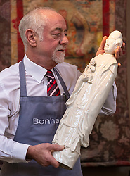 The Bonhams Asian Art Sale takes place on Thursday 15 November at 22 Queen Street Edinburgh starting at 11 am. It features Japanese and Chinese Art including: bronzes, jades, snuff bottles, porcelain, textiles, lacquer, paintings and furniture.<br /> <br /> Pictured: Danny McIlwraith of Bonhams holding a tall Blanc-De_Chine figure of Guanyin and Boy valued between &pound;600 and &pound;800
