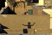 """Young boy flying a kite over the roofs of Cairo's cemetery also called """"city of the dead"""".."""
