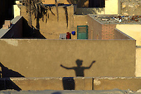 "Young boy flying a kite over the roofs of Cairo's cemetery also called ""city of the dead"".."