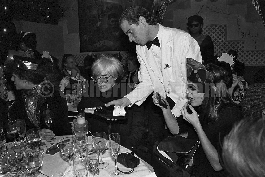 December 31, 1986:  A waiter pours champagne into Andy Warhol's glass as Andy celebrates his last New Year's Eve with a dinner at Cafe Roma restaurant in New York City, New York.  Warhol died less than two months later on February 22, 1987..