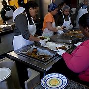 Kitchen volunteers preparing and serving food for the homeless<br />