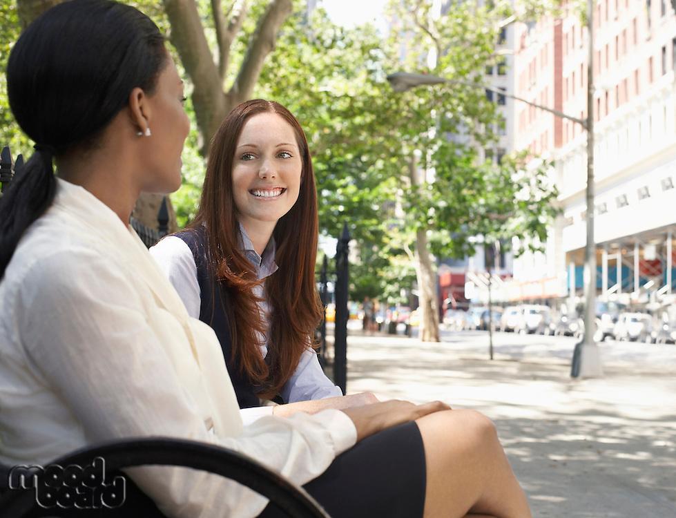 Two female colleagues talking in street