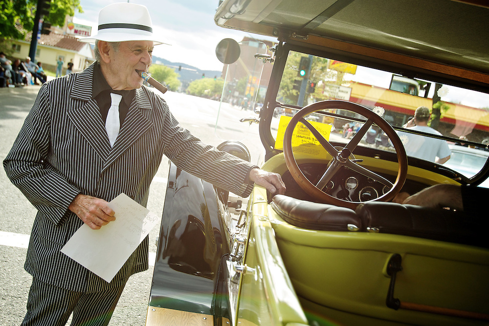 Foster Manning, suited up in 1920's gangster pinstripes, talks to the passengers in his 1925 Dodge while waiting for the start of the Car d'Lane cruise.
