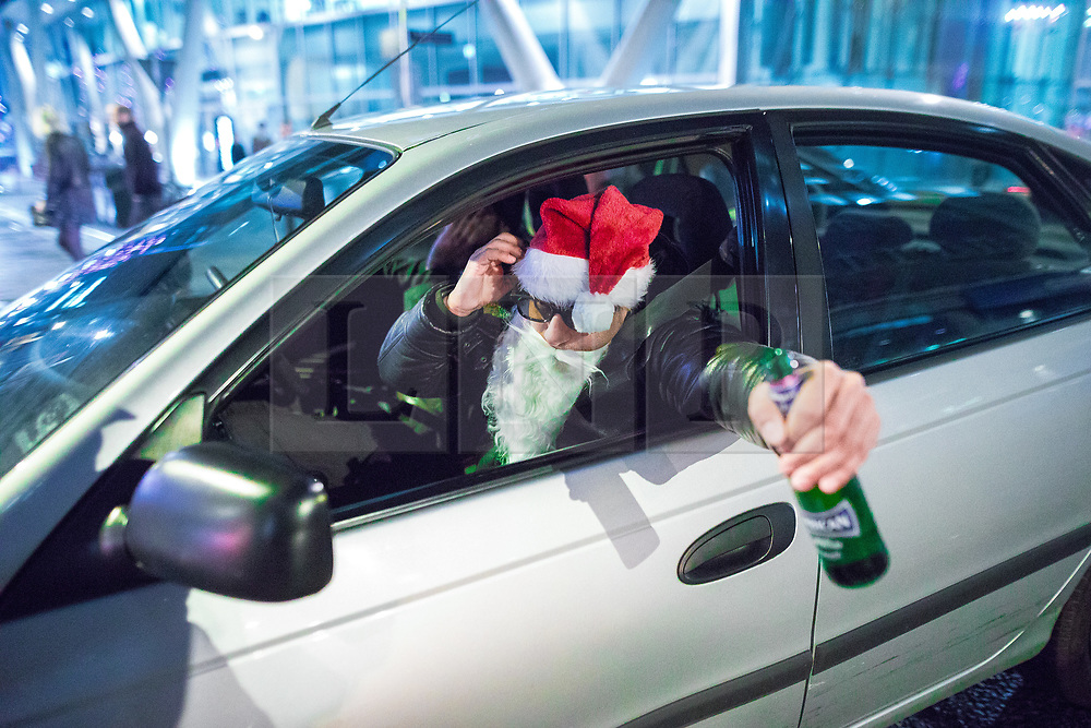 "© Licensed to London News Pictures . 15/12/2017. Manchester, UK. A man dressed as Santa Claus and holding a bottle of beer , leans out of the passenger window of a car on Deansgate . Revellers out in Manchester City Centre overnight during "" Mad Friday "" , named for historically being one of the busiest nights of the year for the emergency services in the UK . Photo credit: Joel Goodman/LNP"