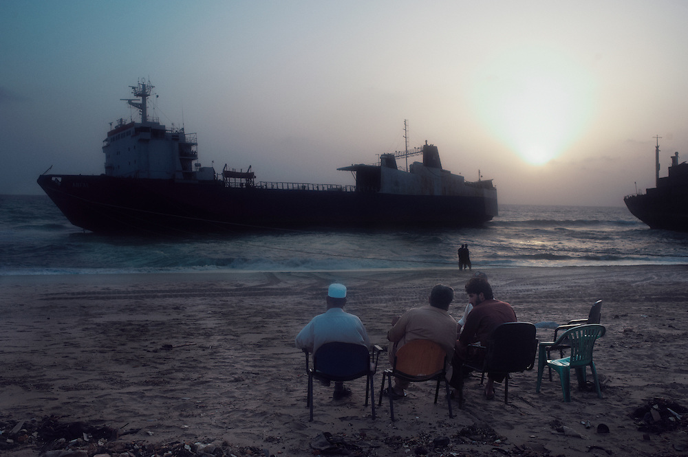 Men sit observing a ship which is being pulled to shore at the  Gadani Ship Breaking Yard, Balochistan Province, Pakistan on August 16, 2011.