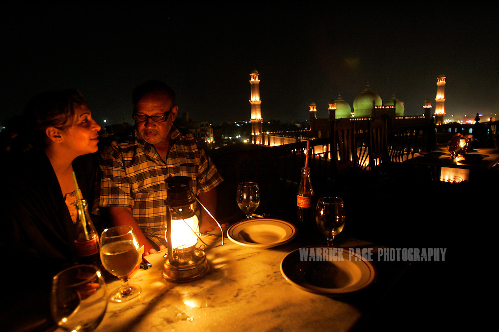 "LAHORE, PAKISTAN - SEPTEMBER 10: Controversial Pakistani artist, Iqbal Hussain, sits on the roof of his restaurant with a ""dancing girl"" (prostitute), September 10, 2006, Lahore, Pakistan. Many girls Iqbal paints often develop strong attachments to him due to the attention they receive. Iqbal grew up in Lahore's red-light district in a brothel with his mother who worked as a ""dancing girl"". Iqbal fell into crime quickly as a youth until his late teens when a chance meeting led him to study painting at the National College of Arts. Breaking free of the more traditional South-Asian style, Iqbal focused his work on painting portraits (including nude) of prostitutes and landscapes of the red-light district. Iqbal has received death threats from hard-line Islamic leaders for displaying his paintings of naked women. His work has since gained acclaim around the world with some of his works auctioned at Sotheby's. (Photo by Warrick Page)"