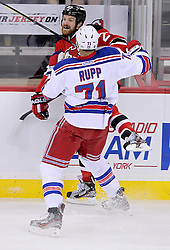 May 19, 2012; Newark, NJ, USA; New York Rangers left wing Mike Rupp (71) hits New Jersey Devils right wing David Clarkson (23) during the first period in game three of the 2012 Eastern Conference Finals at the Prudential Center.