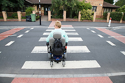 Woman wheelchair user using a zebra crossing,