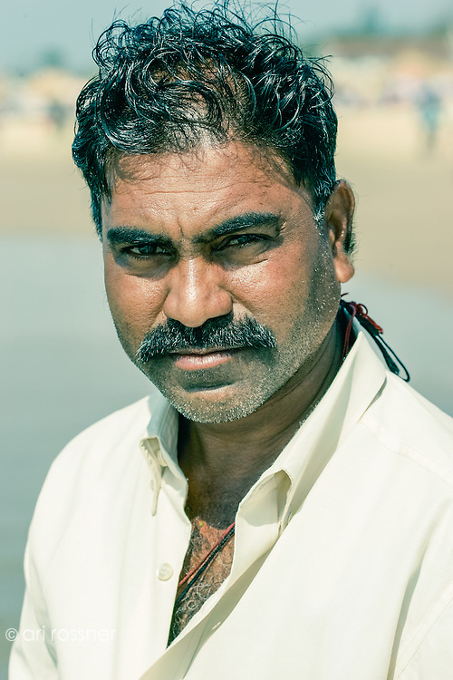 Portrait of a man with a white shirt looking at the camera, on the beach