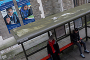 Oasis Academy students appear on posters above a bus stoip in the south London borough of Lambeth, where passengers of different ages sit waiting for the next bus, on 6th February 2018, in London, England.