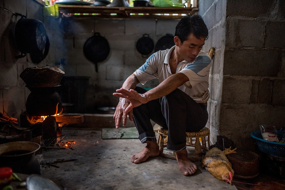 A man looks at the chicken he will cook for dinner in the village of Khoc Kham. The village is not connected to the main electrical grid and many residents operate their own turbines to power lights and sometimes small appliances.